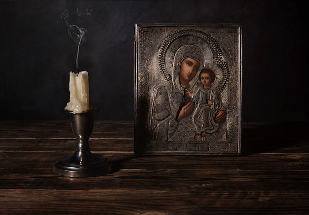 Vela apagada em frente a um antigo ícone ortodoxo de nossa senhora de iver
