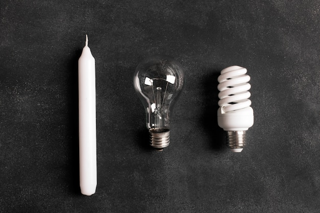 Vela branca e lâmpadas elétricas no fundo preto