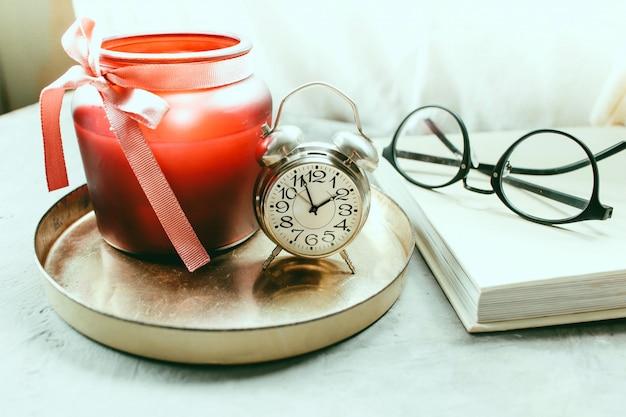 Vela brilhante ao lado de uma bandeja de ouro ao lado de uma xícara de café e uma bela panela mobiliário doméstico atmosfera acolhedora