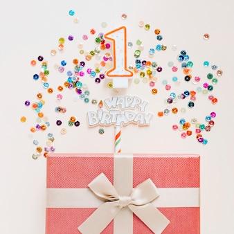 Vela de aniversário com presente rodeado de lantejoulas
