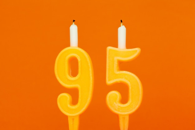 Vela de aniversário de cera colorida em fundo laranja
