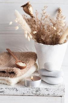 Vela de aroma acesa bege e flores secas douradas na mesa rústica. arranjo de spa com sal em estilo monocromático