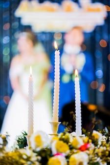 Vela de casamento e noiva, noivo em cerimônia
