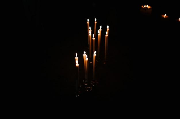 Vela de cera acesa no escuro na igreja