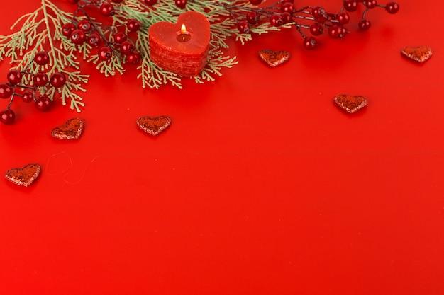 Vela de coração com bagas na mesa