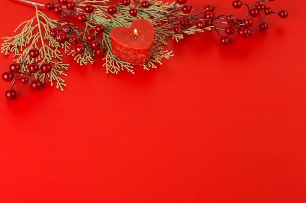 Vela de coração com bagas vermelhas na mesa