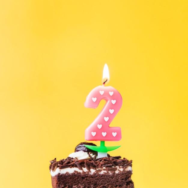 Vela de dois anos de amor iluminado na fatia de bolo sobre fundo amarelo