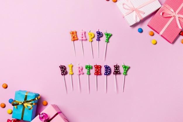 Vela de feliz aniversário varas com caixas de presente e pedras preciosas em pano de fundo rosa