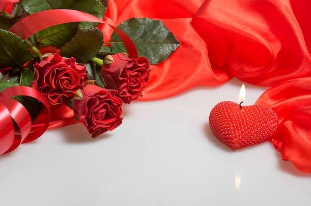 Vela de forma de coração e buquê de rosas vermelhas em branco