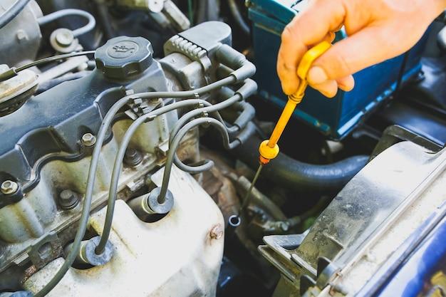 Vela de ignição no motor de um carro antigo. homem verificando o nível de óleo no tanque. detalhes internos da máquina. reparação de veículo.