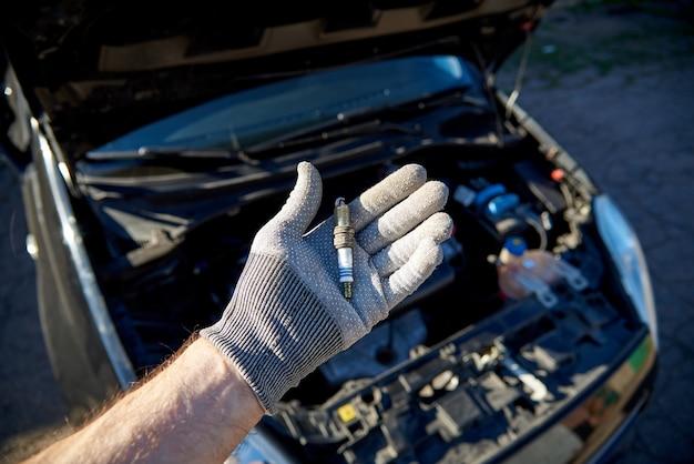 Vela de ignição para o motor na mão masculina, carro com um capô aberto.