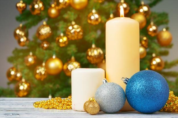 Vela de natal acesa contra o fundo da árvore de peles decoradas