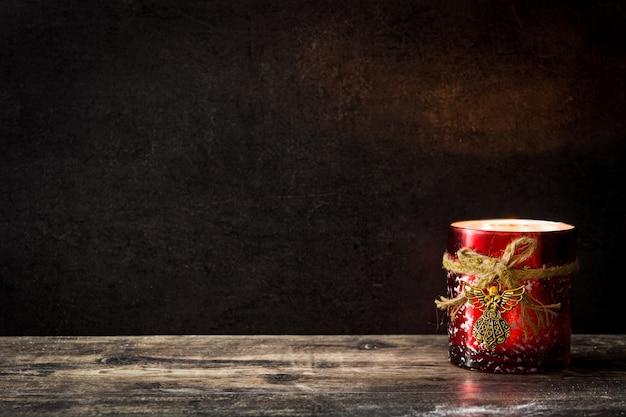 Vela de natal na mesa de madeira e preto. copie o espaço