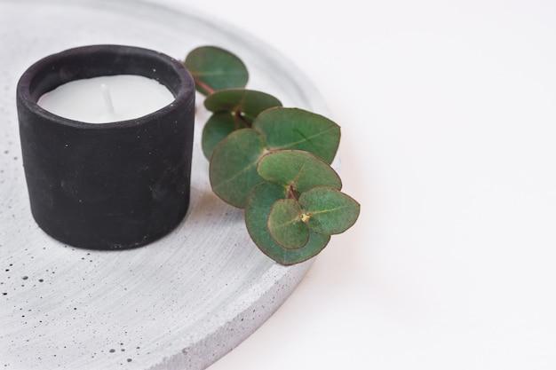 Vela de pedra preta ramo seco de eucalipto verde sobre fundo branco