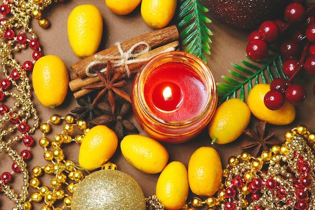 Vela, decorações de natal, canela e kumquat