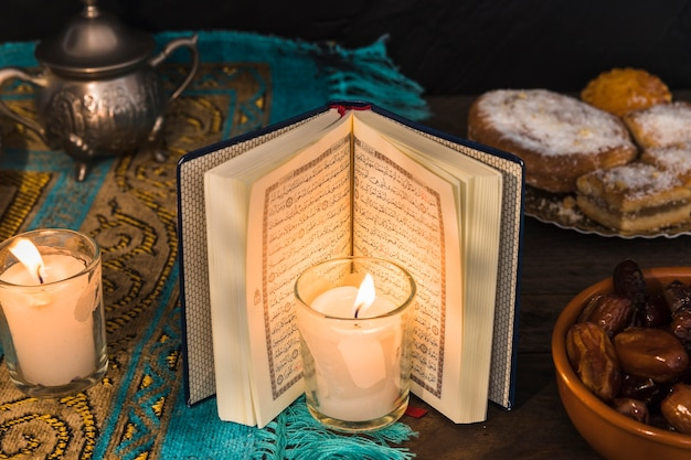 Vela e livro árabe perto de sobremesas