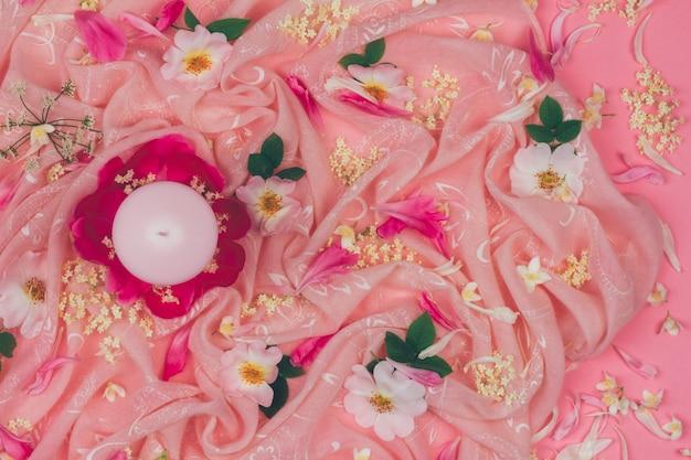 Vela e rosa flores rosas selvagens no fundo da tela-de-rosa, vista plana leigo