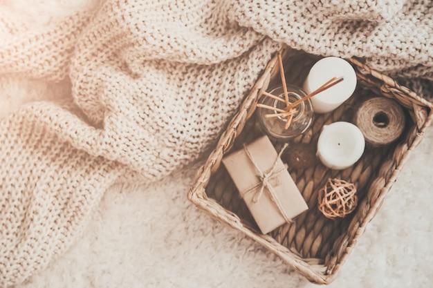 Vela e roupas de tricô em cesta de vime