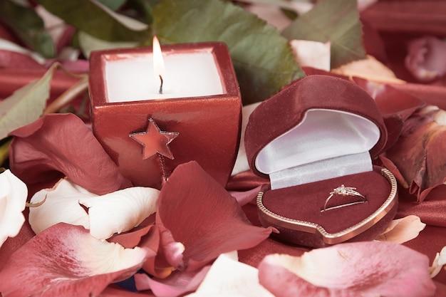 Vela e um anel de diamante em um fundo de pétalas de rosa