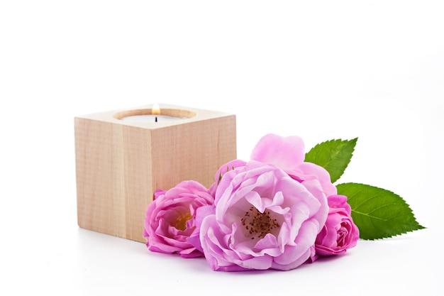 Vela em um suporte de vela de madeira e buquê de rosas rosa selvagem isolado na superfície branca