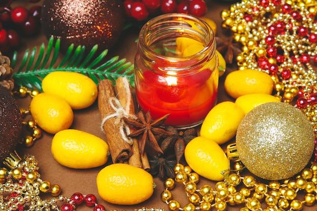 Vela, enfeites de árvore de natal, canela e kumquat