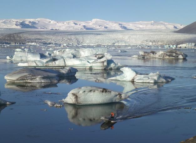 Vela entre os icebergs hugh na lagoa glaciar de jokulsarlon do sul da islândia