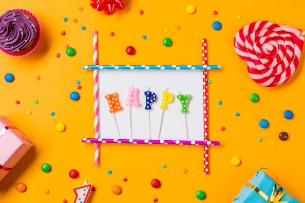 Vela feliz com muffins; gemas; granulados; caixas de presente e pirulito de forma de coração em um pano de fundo laranja