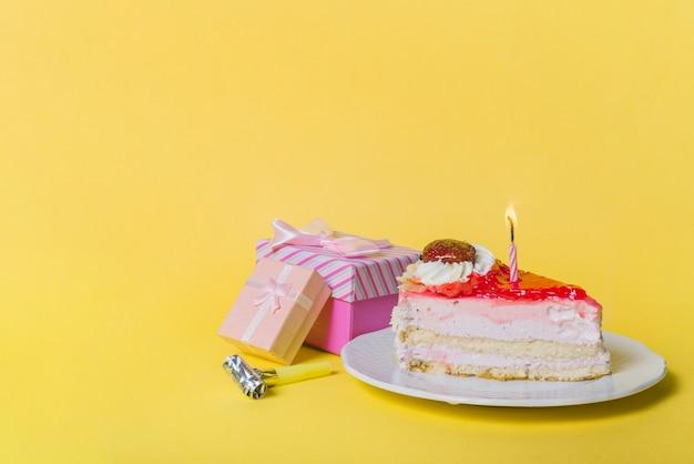 Vela iluminada no bolo da fatia com duas caixas de presente e ventilador do partido contra o fundo amarelo