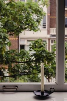 Vela longa e branca em um castiçal vintage de estilo antigo em pé na grande janela de madeira