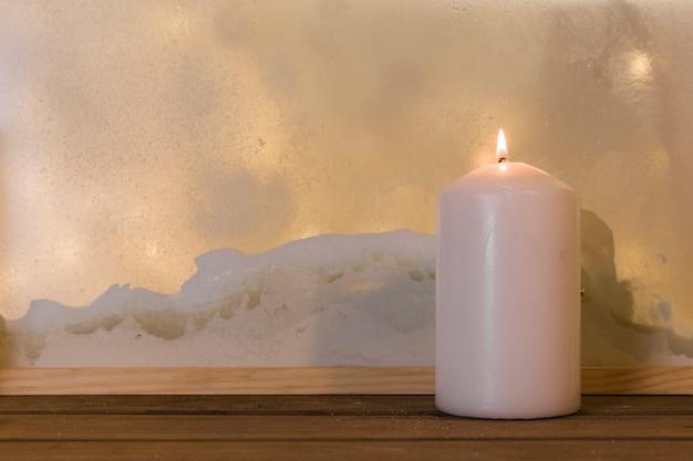 Vela na placa de madeira perto da pilha de neve pela janela