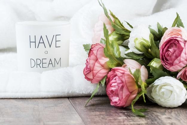 Vela na toalha branca fofa ao lado de rosas brancas e rosa em uma superfície de madeira