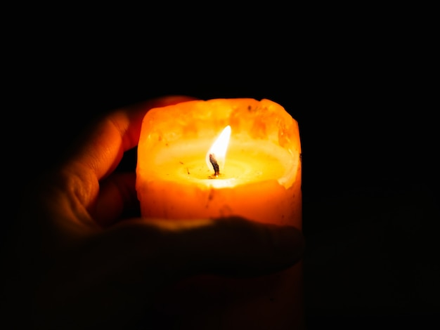 Vela nas mãos em uma parede escura. durante o festival da luz