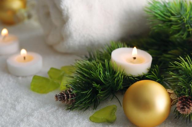 Vela no galho de pinheiro e decorações de natal, close-up