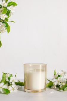 Vela perfumada com flores de cerejeira na mesa de aromaterapia de fragrâncias caseiras