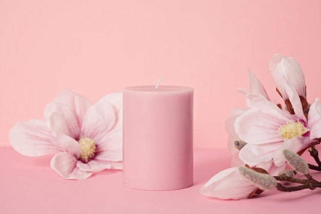 Vela perfumada de flores delicadas sobre fundo rosa pastel