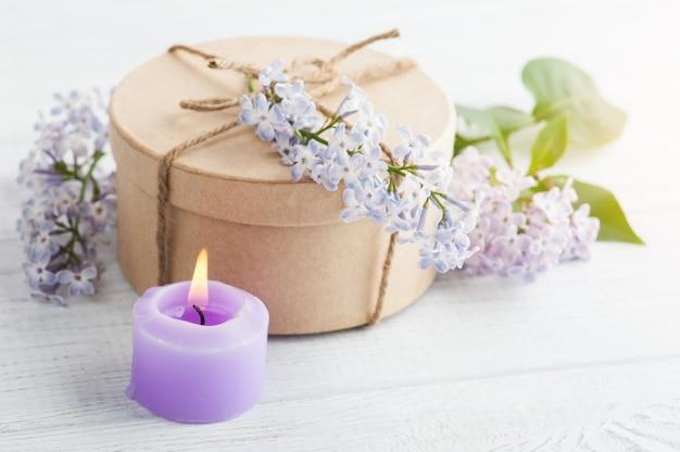Vela roxa acesa e flores lilás