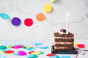 Vela sobre a fatia de bolo e confetes na mesa
