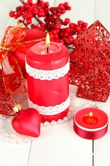 Vela vermelha com decoração de natal em fundo claro