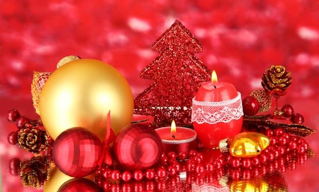 Vela vermelha com decoração de natal em superfície brilhante