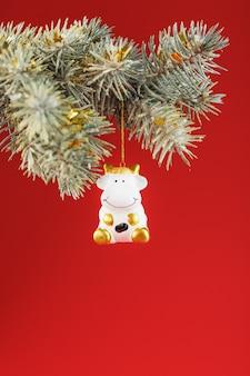 Vela vermelha de boi branco e galho de árvore de natal
