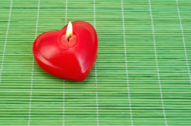 Vela vermelha em forma de coração em uma esteira de bambu verde