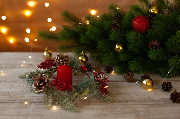 Vela vermelha, grinalda perto da árvore de natal