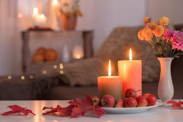 Velas acesas com decoração de outono na mesa branca em casa