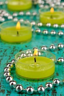 Velas acesas com miçangas na superfície verde