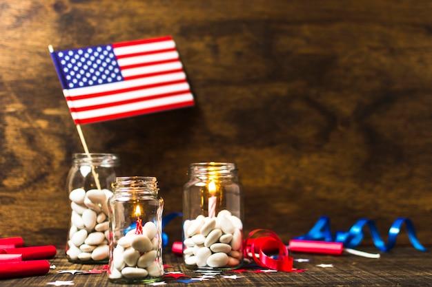 Velas acesas e bandeira eua no pote de doces na mesa de madeira