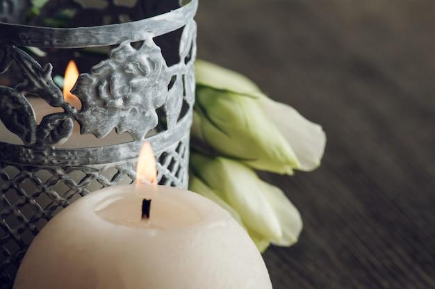 Velas acesas e flores brancas na mesa rústica escura