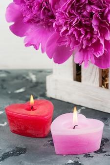 Velas acesas em forma de coração, peônias roxas