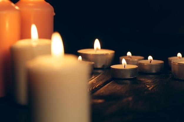 Velas acesas na escuridão sobre o preto. comemoração.