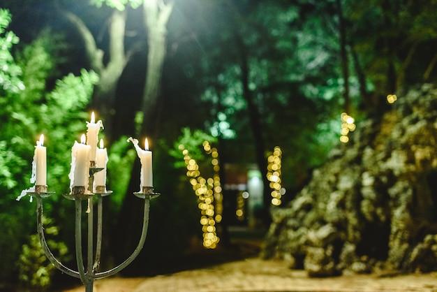 Velas acesas para iluminar um jardim durante um jantar à noite.
