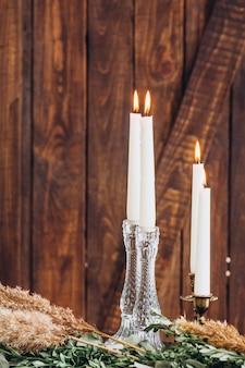 Velas altas brancas em castiçais de cristal no fundo texturizado de madeira rústico.